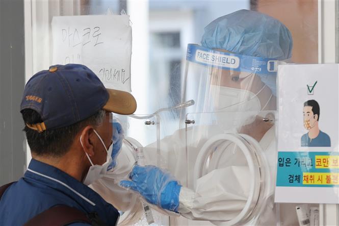 Nhân viên y tế lấy mẫu xét nghiệm COVID-19 tại Seoul, Hàn Quốc, ngày 20/6/2021. Ảnh: YONHAP/TTXVN