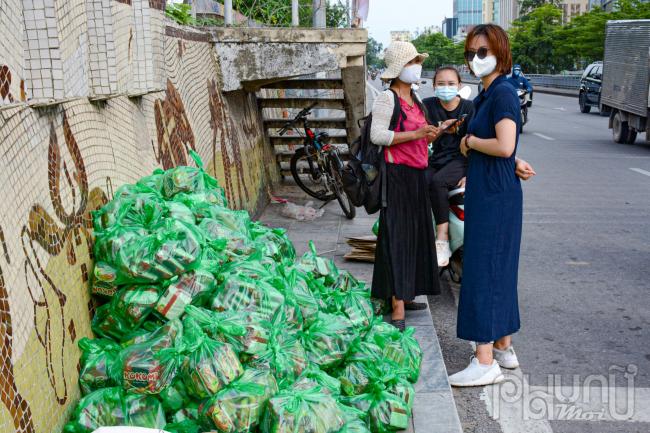 Đội thiện nguyện đang chờ tới lượt đưa mì tôm vào tiếp tế cho người dân.