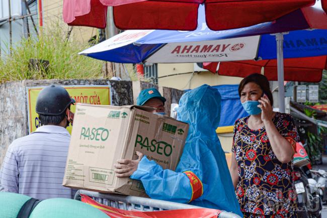 Lực lượng chức năng mặc đồ bảo hộ nhận lương thực tiếp tế qua rào chắn.