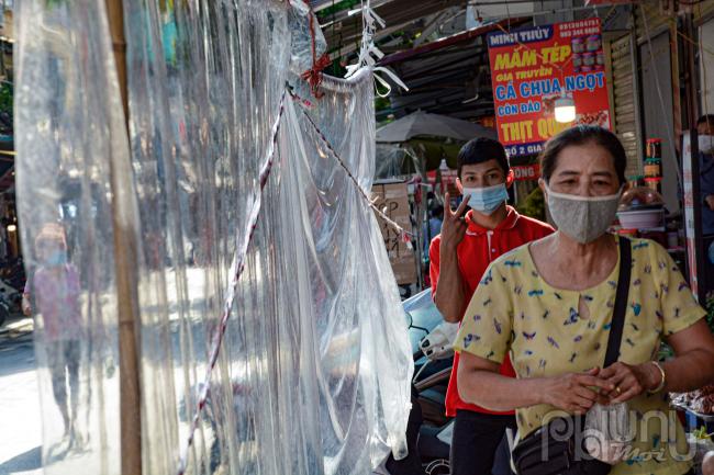 Các cửa hàng gần cửa tiếp xúc nhiều nên người dân căng tấm nilon chắn đảm bảo khoảng cách mua hàng.