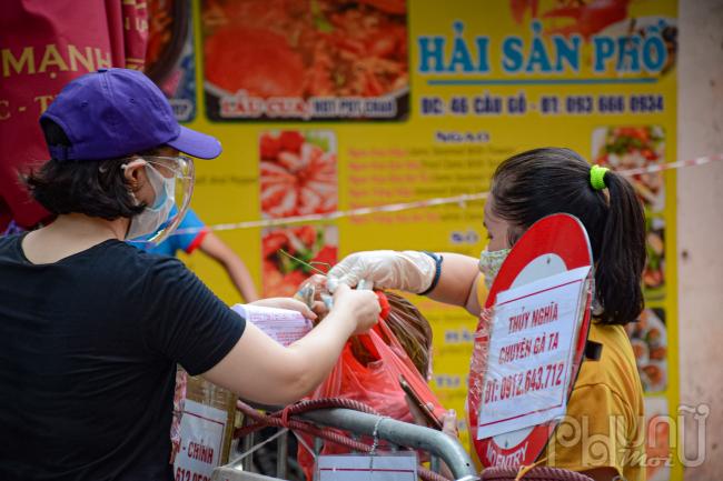 Thực phẩm được các tiểu thương trong chợ mang ra tận khu vực rào chắn phục vụ.