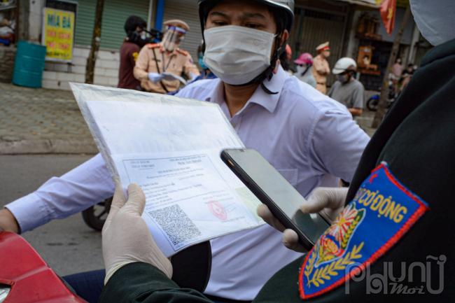 Lực lượng chức năng tiến hành quét mã QR code với giấy đi đường mới bằng điện thoạikiểm tra thông tin.