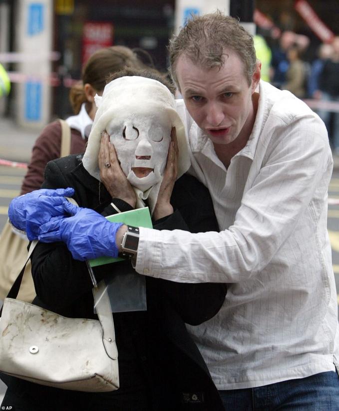 """Paul Dadge đang hỗ trợ một phụ nữ là nạn nhân của vụ đánh bom tàu và xe bus ngày 7/7/2005 ở London, vụ tấn công đầu tiên của một nhóm Hồi giáo cực đoan trên đấtAnh. Báo chí đã gọi người được cứu trợ là """"người phụ nữ bịt mặt"""". Ảnh:Press Association"""