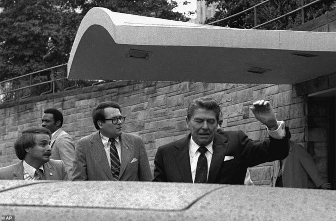 Tổng thống Mỹ Ronald Reagan đang giơ tay thì bị ám sát bên ngoài một khách sạn ở Washington vào ngày 30/3/1981. Ảnh:AP.