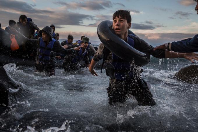 Ngày 1 tháng 10 năm 2015. Sau khi chiến đấu với biển động và gió lớn từ Thổ Nhĩ Kỳ, những người di cư đến bằng bè cao su trên một bờ biển lởm chởm đá của đảo Lesbos (Hy Lạp). Sợ bè bị lật hoặc đâm thủng, một số người hoảng loạn và nhảy xuống nước lạnh trong tuyệt vọng đểchạy vàođất liền.  (Ảnh của Tyler Hicks)