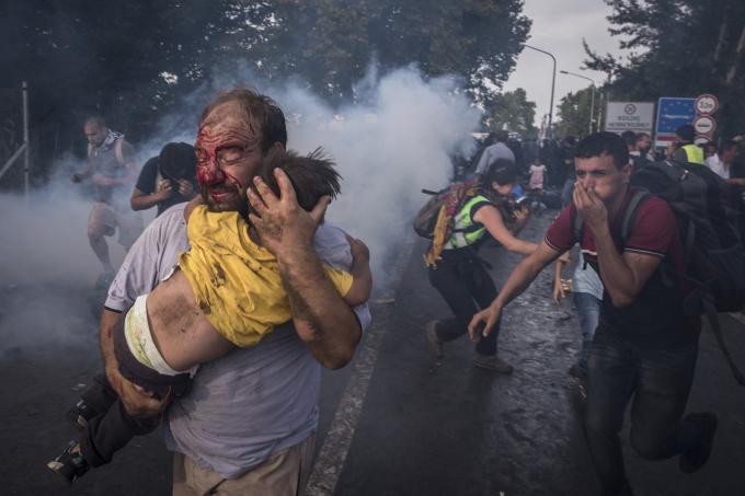 Ngày 16 tháng 9 năm 2015. Một người đàn ông cố gắng che chắn cho con mình khỏi bị cảnh sát đánh đập và xịt hơi cay tại cửa khẩu biên giới ở Horgos, Serbia. Cảnh sát chống bạo động Hungary cầm dùi cui phóng ra hơi cay và vòi rồng chống lại hàng trăm người di cư sau khi họ vượt qua hàng rào dây thép gai và cố gắng xông vào Hungary từ Serbia.  (Ảnh củaSergey Ponomarev)