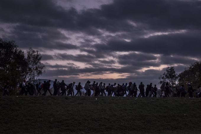 Ngày 23 tháng 10 năm 2015. Người di cư đi bộ dọc theo một con đê, được hộ tống bởi cảnh sát chống bạo động người Slovenia, đến một trạitị nạnbên ngoài Dobova. Thời tiết lạnhvà những tấm biểncảnh báonguy hiểm không thể hạn chếlàn sóng người tị nạn.  (Ảnh củaSergey Ponomarev)