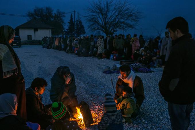 Ngày 21 tháng 11 năm 2015. Một gia đình tị nạn từ Syria sưởi ấm quanh đống lửa, những người khác đang xếp hàng để được đăng ký tại một trại tị nạn ở Gevgelija.  (Ảnh của Mauricio Lima)