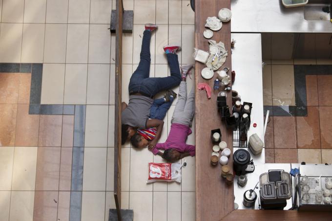 Mọi người ẩn nấpphía sau một quầy tại trung tâm mua sắm Westgate sau vụ xả súng ở Nairobi, Kenya, vào tháng 9 năm 2013. Nhóm khủng bố Somalia Al-Shabaab, một chi nhánh của al Qaeda, nhận trách nhiệm vềmột cuộc bao vây đẫm máu kéo dài bốn ngày tại trung tâm mua sắm cao cấp.Ít nhất 67 người đã thiệt mạng. Ảnh: Tyler Hicks / Thời báo New York / Redux
