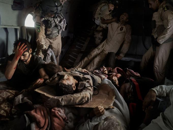 Vào tháng 8 năm 2014, một máy bay trực thăng cung cấp viện trợ cho thường dân Yazidibị mắc kẹt bởi phiến quân ISISđã bị rơi ở dãy núi Sinjar ở miền bắc Iraq.Trong bức ảnh này, những người sống sót sau vụ tai nạn được đưa lên một chiếc trực thăng cứu hộ thứ hai đi đến lãnh thổ của người Kurd.Phi công thiệt mạng trong vụ tai nạn nằm dưới người bị thương. Hình ảnh Moise Saman / Magnum