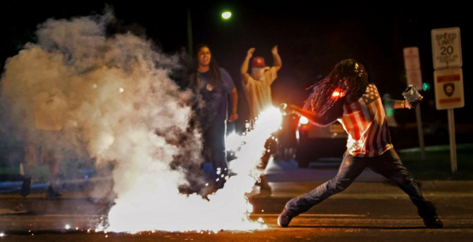 Edward Crawford ném trả một ống đựng hơi cay do cảnh sát bắn ra khi cảnh sát đang cố gắng giải tán người biểu tình ở Ferguson, Missouri, vào tháng 8-2014. Một số cuộc biểu tình trong thành phố đã biến thành cuộc đụng độ giữa những người dân và cảnh sát sau vụ việc thanh niên da màu Michael Brown không trang bị vũ khí, bị cảnh sát da trắng Darren Wilson bắn chết - Ảnh: AP