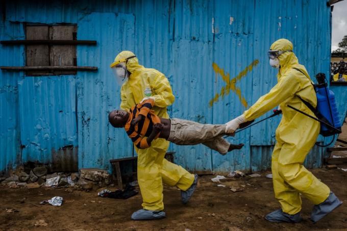 Các nhân viên y tế ở Monrovia, Liberia, mang theo James Dorbor, một đứa trẻ 8 tuổi bị nghi nhiễm virut Ebola, vào một cơ sở điều trị vào tháng 9 năm 2014. Tây Phi đang đối phó vớidịch Ebola bùng phát nguy hiểm nhất.Vụ dịch kết thúc vào năm 2016 sau hơn 11.000 ca tử vong. Ảnh: Daniel Berehulak / Thời báo New York / Redux