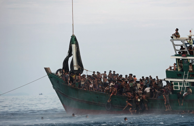 Những người di cư Rohingya nhảy khỏi thuyền để thu thập nguồn thực phẩm được cung cấp bởi quân đội Thái Lan từ một chiếc trực thăng vào tháng 5-2015. Chiếc thuyền nhồi nhét rất nhiều người di cư và trôi dạt trong vùng biển Thái Lan. Hơn 740.000 người Rohingya đã trốn sang nước láng giềng Bangladesh sau khi quân đội Myanmar tiến hành chiến dịch bạo lực chống lại người thiểu số Hồi giáo. Myanmar cho rằng hành động của họ là đúng và mục tiêu của họ là những kẻ khủng bố - Ảnh: AFP