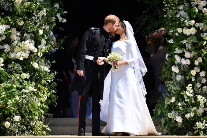 Hoàng tử Anh Harry và người vợ mới cưới, Meghan, hôn nhau trên các bậc thang của nhà thờ St. George ngay sau khi kết hôn ở Windsor, Anh, vào tháng 5-2018 - Ảnh: Getty Images