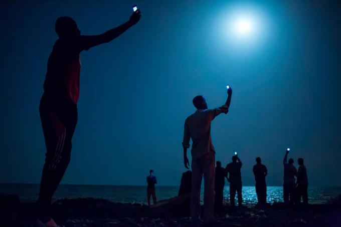 Những người di cư châu Phi tại Djibouti giơ điện thoại để cố bắt tín hiệu rẻ tiền từ nước láng giềng Somalia vào tháng 2-2013. Djibouti là điểm dừng chân phổ biến của những người di cư châu Phi muốn tìm kiếm cuộc sống tốt hơn tại châu Âu và Trung Đông - Ảnh: National Geographic