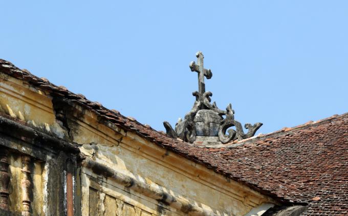Trang trí góc đỉnh mái với thánh giá nhưng vẫn gợi hình ảnh quen thuộc nậm rượu hoặc bốn lá cúc xếp chụm trên các đỉnh trụ ở đình, chùa. Sát gần đó là một vết nứt nghiêm trọng xẻ dọc tường.