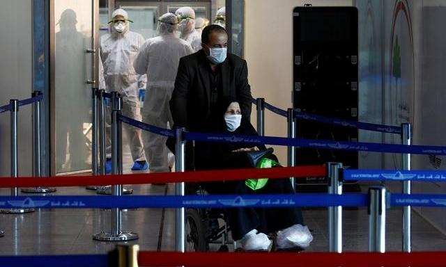 Hành khách đi từ Iran đến sân bay Najaf ở Iraq ngày 5/3. Ảnh:Reuters.