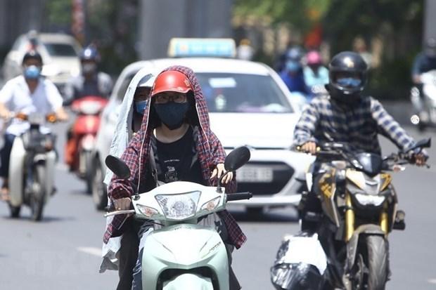 Người dân cần trang bị các vật dụng chống nắng khi ra đường. (Ảnh: Minh Quyết/TTXVN)
