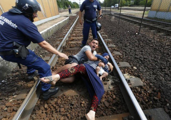 Cảnh sát ngăn cản một gia đình di cư bỏ chạy tại nhà ga ở thị trấn Bicske, Hungary.