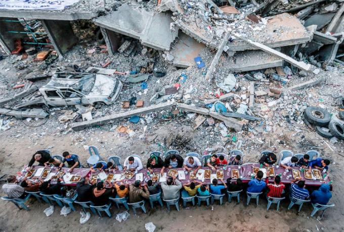 Các gia đình Palestine ăn uống cạnh một tòa nhà bị phá hủy trong cuộc giao tranh giữa lực lượng Hamas và Israel ở Dải Gaza ngày 18/5, trong tháng Ramadan của người Hồi giáo. Ảnh:Mahmud Hams/AFP
