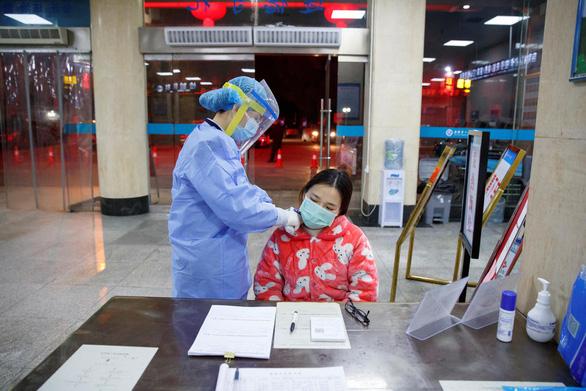 Nữ nhân viên y tế đo thân nhiệt một phụ nữ tại một bệnh viện ở tỉnh Hồ Nam, giáp ranh tỉnh Hồ Bắc, nơi bùng phát các ca nhiễm virus Corona mới đầu tiên ở Trung Quốc, vào ngày 28/1.