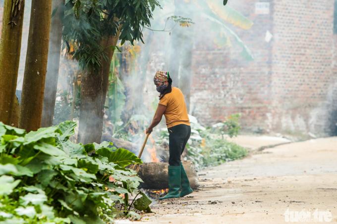 Một người dân đốt rác thải bên cạnh ngôi nhà có người bị nhiễm virus corona.