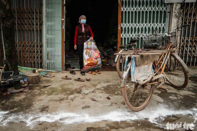 Bà Phạm Thị Trang, một người dân tại thôn Ái Văn, rắc vôi bột khử trùng trước cửa nhà. Từ ngày trong thôn có người bị nhiễm virus corona, bà hạn chế ra đường. Khi đưa hàng cho các hộ gia đình ở các xã khác, các bạn hàng cũng yêu cầu bà Trang đặt hàng ở phía ngoài, họ tự ra lấy, hạn chế tiếp xúc trực tiếp.