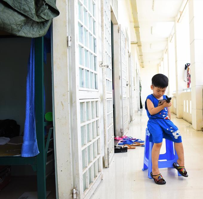 Một bé trai xem điện thoại ngoài hành lang tại một dãy phòng thuộc khu cách ly ở trường quân sự TP.Cần Thơ. Ảnh: Laodong.vn
