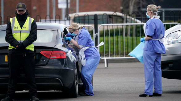 Nhân viên y tế Anh phết dịch mũi họng của người dân để xét nghiệm - Ảnh: Sky News
