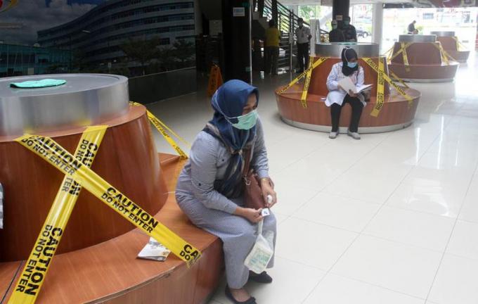 Người dân Indonesia đến bệnh viện Padang, tỉnh West Sumatera ngồi chờ trên những hàng ghế đặc biệt được dán băng keo để đảm bảo mọi người không ngồi sát nhau.