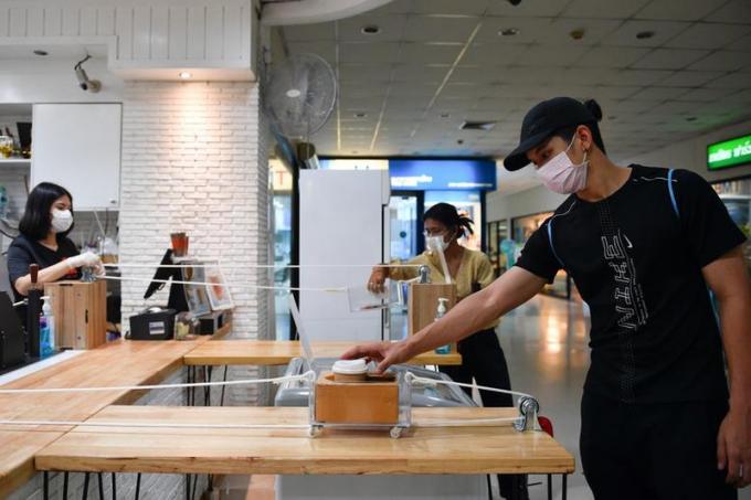 Một khách hàng nhận cafe đặt trong hộp được chuyển bằng một hệ thống dây tự chế của một quán cafe tại Bangkok, Thái Lan.