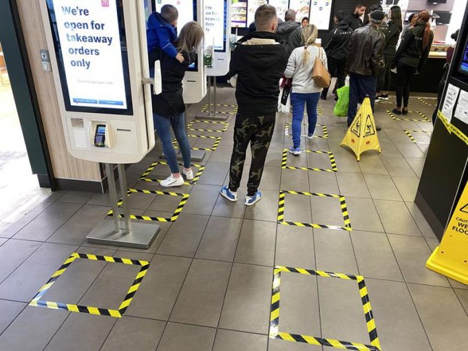 Mọi người xếp hàng theo những ô vuông được kẻ sẵn để tạo khoảng cách tại trung tâm thương mại Brent Cross ở London, Anh.