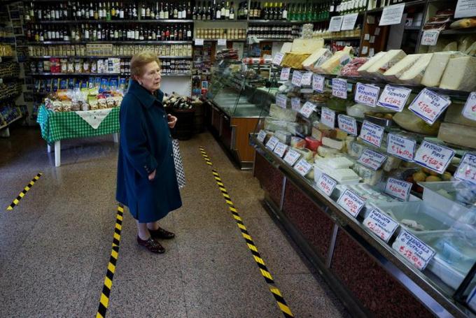 Một cụ bà đứng chờ ở vạch kẻ tại một cửa hàng thực phẩm ở Rome, Italy.