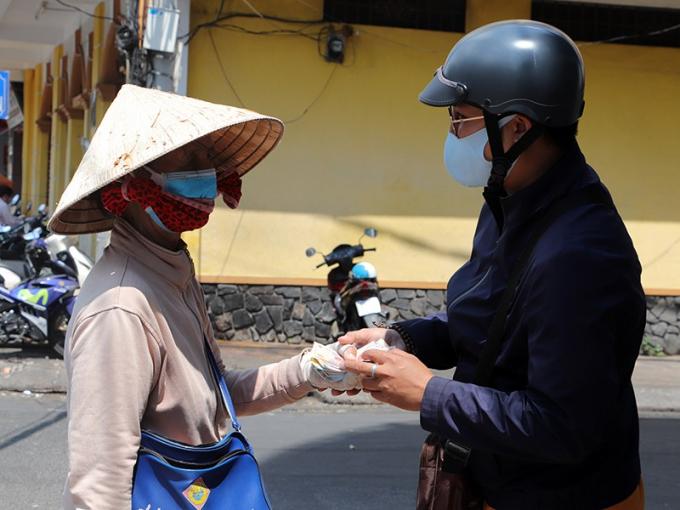 Anh Ngôn Thắng (phải) vận động hỗ trợ tiền cho những người bán vé số, mỗi người 200.000 đồng. Ảnh: PLO.
