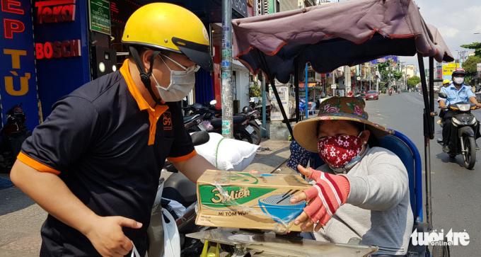 Người phụ nữ quê ở An Giang lên Sài Gòn mưu sinh bằng nghề bán vé số vui mừng khi nhận được phần quà nhỏ để duy trì cuộc sống những ngày sắp tới.Ảnh:Tuổi Trẻ