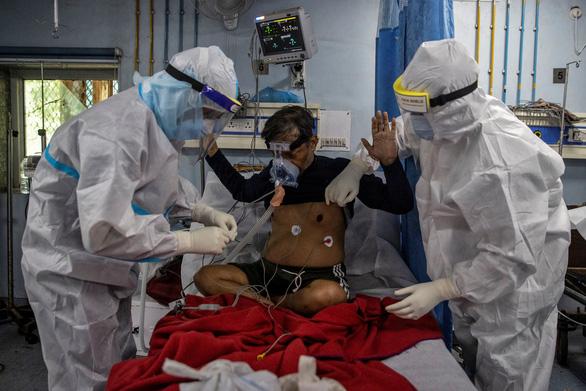 Một bệnh nhân COVID-19 ở Ấn Độ được hai nhân viên y tế hỗ trợ khi đang nằm trong phòng chăm sóc đặc biệt.Ảnh:Reuters.