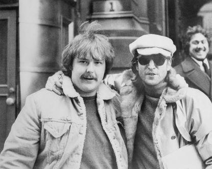 Tay máy nghiệp dư Paul Goresh (trái) chụp hình cùngJohn Lennon chỉ vài giờ trước khi huyền thoại này bị sát hại ngày 8/12/1980. Tình cờ là đằng sau họ chính làMark David Chapman - kẻ sau đó đã nã súng vào thần tượng của mình lúc 22h50p (giờ Bắc Mỹ)