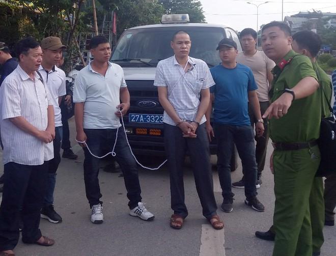 Vì Văn Toán (đeo còng số 8) tại buổi thực nghiệm điều tra. Ảnh: Thu Trang.