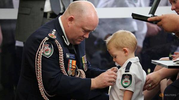 Ủy viên Cơ quan Cứu hỏa Nông thôn bang New South Wales, đã quỳ gối và đeo chiếc huân chương lên ngực áo của Harvey.