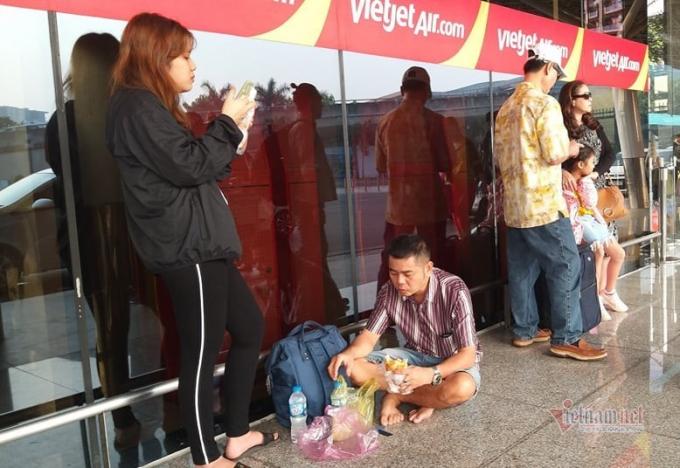 Nhiều người còn phải tranh thủ ăn vì chờ đợi lâu (Ảnh: Vietnamnet)