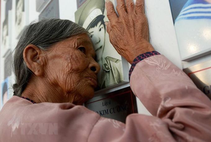 Người phụ nữ này là bà Hà Thị Liên (quê Can Lộc, Hà Tĩnh), mẹ liệt sỹ Đào Kim Cương. Đây là nơi đặt diảnh con trai của ở khu lưu niệm di vật liệt sỹ Gạc Ma trong Khu tưởng niệm chiến sỹ Gạc Ma ở xã Cam Hải Đông, huyện Cam Lâm (tỉnh Khánh Hòa).