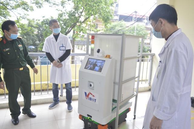 PGS.TS. Đại tá Tăng Quốc Nam, Chủ nhiệm đề tài (bìa trái) giới thiệu robot tới các bác sĩ bệnh viện Bắc Thăng Long.