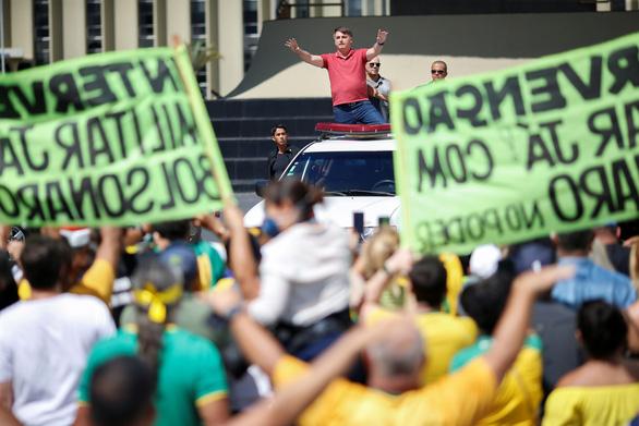 Tổng thống Brazil Jair Bolsonaro chào những người ủng hộ, người biểu tình. Ảnh: REUTERS