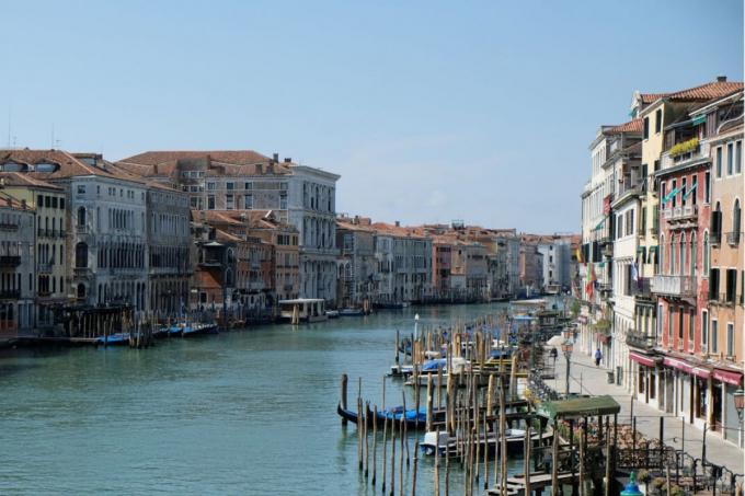 Khu vực kênh đào Grand, Venice, Italy được chụp vào ngày 6/1/2018 (ảnh 1) và ngày 17/4/2020 (ảnh 2) cho thấy sự khác biệt về chất lượng không khí. Bầu trời trong xanh hơn, tầm nhìn rõ hơn. Nhờ vào việc giảm lưu lượng giao thông đường thủy và nước trong sạch tới mức có thể nhìn thấy tận đáy. Thị trưởng thành phố cho biết do ít tàu thuyền đi lại, bùn và cặn đã lắng xuống dưới. Ảnh: Manuel Silvestri/Reuters.