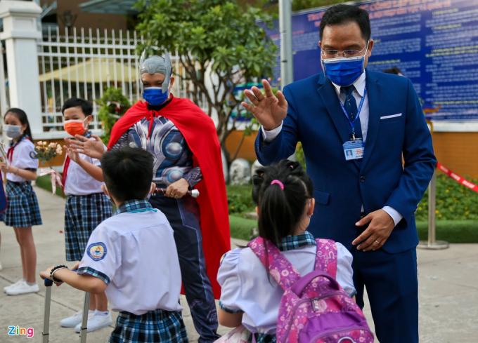 Từ 6h30 ngày 11/5, giáo viên trường tiểu học Lê Đức Thọ (quận Gò Vấp, TP.HCM)hóa trang thành anh hùng siêu nhân, công chúa... đón các em học sinh trở lại trường sau thời gian dài nghỉ phòng dịch. Hình ảnh khiến nhiều em nhỏ thích thú.