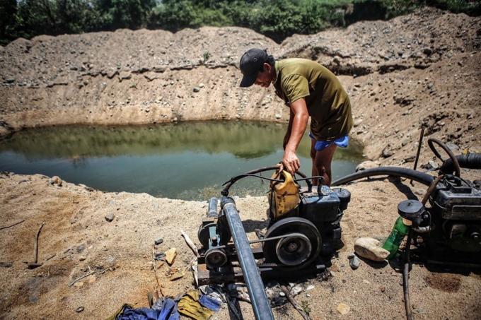 Người dân bơm nước từ những hố được đào sâu xuống đáy sông Lu, huyện Thuận Nam để lấy nước sinh hoạt và tưới tiêu do hạn hán kéo dài. (Ảnh: TTXVN)