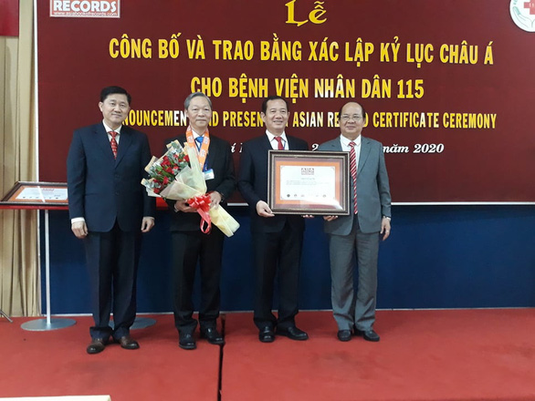 Bác sĩ Phan Văn Báu - giám đốc Bệnh viện Nhân dân 115 (thứ 2 phải qua) và bác sĩ Chu Tấn Sĩ (thứ 3 phải qua) nhận chứng nhận kỷ lục từ Tổ chức kỷ lục Việt Nam - Ảnh: HOÀNG LỘC