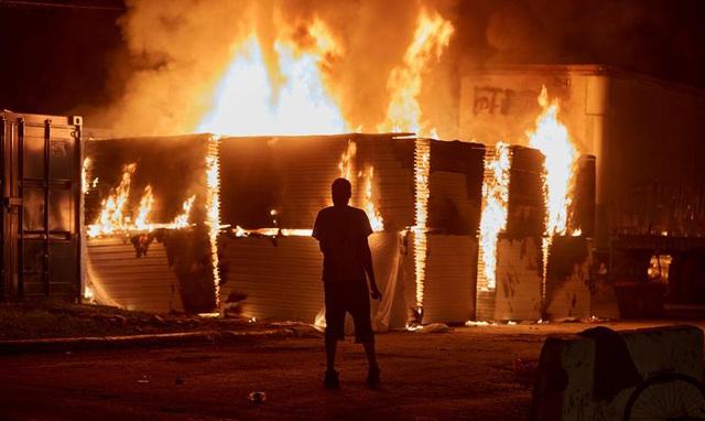Người biểu tình đứng trước một tòa nhà đang bị hỏa hoạn nằm gần trụ sở cảnh sát Minneapolis.