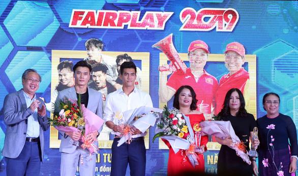 Thủ môn Bùi Tiến Dũng, Nguyễn Tiến Linh nhận giải thưởng cho U22 Việt Nam. Bên cạnh là hai CĐV đã mang 60kg thức ăn sang tiếp tế cho cả đội tuyển - Ảnh: N.K.