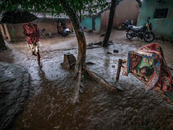 Khoảnh khắc những đứa trẻ Ấn Độ trú mưa trên chiếc chõng tre đã được nhiếp ảnh gia Sourav Das ghi lại. Sourav Das cho biết những đứa trẻ này đang chơi thì trời đổ mưa nên phải trú ở đây,chúng đang đợi bố đón về.